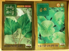 Aster scaber and Ligularia fischeri seed packets -- Aster scaber and Ligularia fischeri seed packets from a Korean vegetable seed catalogue. When I first posted this picture on FB, a Korean friend,  Woo Lee, recognising the plants told me that these two plants are used very differently in Korea:   곰취 or Ligularia fischeri is eaten raw,  without cooking or steaming. On the other hand, 산내들 취나물 or Aster scaber is steamed or lightly boiled. Hea also told me that both need acool shade place with moisture, perfect forest garden plants in other words!